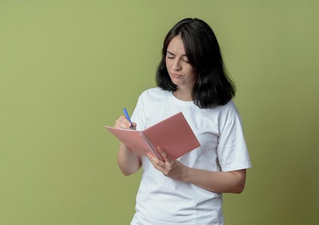 Onbehaagd jong vrij kaukasisch de pen en het blocnote van de meisjesholding die iets schrijven dat op olijfgroene achtergrond met exemplaarruimte wordt geïsoleerd