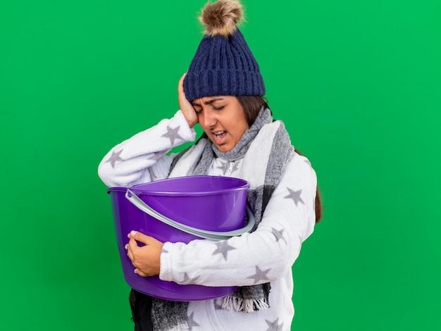 Onbehaagd jong ziek meisje dat de winterhoed met sjaal draagt die plastic emmer houdt die hand op oog zet dat op groene achtergrond wordt geïsoleerd