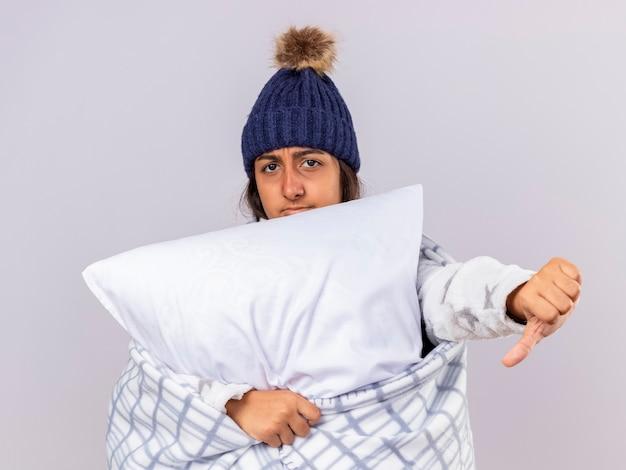 Onbehaagd jong ziek meisje dat de wintermuts met sjaal draagt die in geruite knuffelen kussen wordt verpakt die duim neer toont