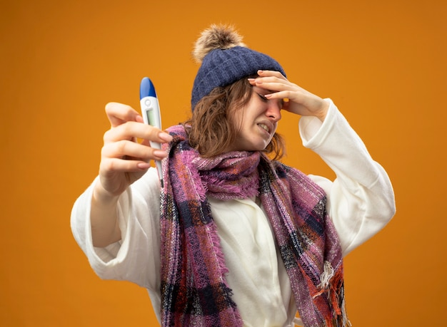 Onbehaagd jong ziek meisje dat een wit gewaad en een wintermuts draagt met een sjaal die een thermometer vasthoudt die de hand op het voorhoofd zet geïsoleerd op een oranje muur