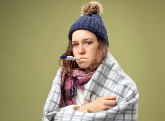 Onbehaagd jong ziek meisje dat wit gewaad en wintermuts met sjaal draagt die in plaid wordt verpakt die thermometer in mond zet die op olijfgroen wordt geïsoleerd