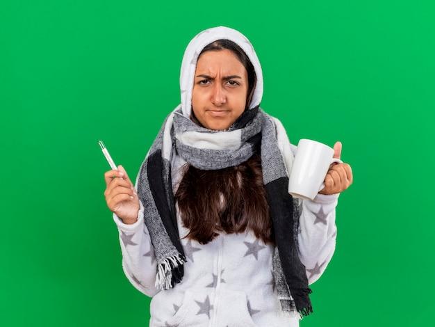 Onbehaagd jong ziek meisje die op de thermometer van de de sjaalholding van de kap wearin met kop thee zetten die op groen wordt geïsoleerd