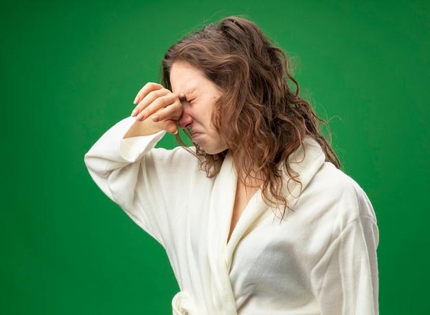 Onbehaagd jong ziek meisje met gesloten ogen, gekleed in een wit gewaad afvegende neus met hand geïsoleerd op groen