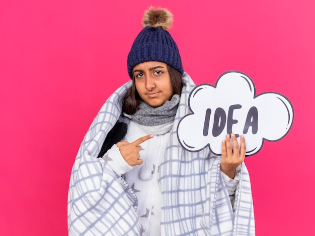 Onbehaagd jong ziek meisje met wintermuts met sjaal gewikkeld in geruite bedrijf en wijst op idee zeepbel geïsoleerd op roze achtergrond