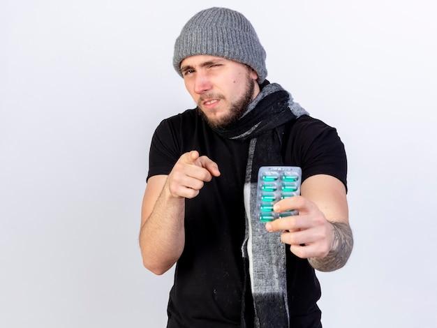 Onbehaagde jonge blanke zieke man met winter hoed en sjaal houdt pakje medische capsules en punten geïsoleerd op een witte muur met kopie ruimte