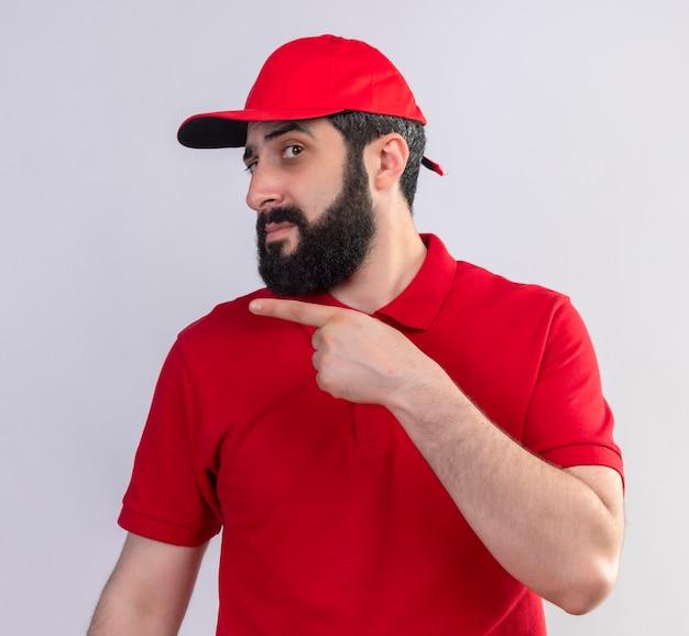 Onbehaagde jonge knappe blanke bezorger met rode uniform en pet wijzend naar kant geïsoleerd op een witte achtergrond