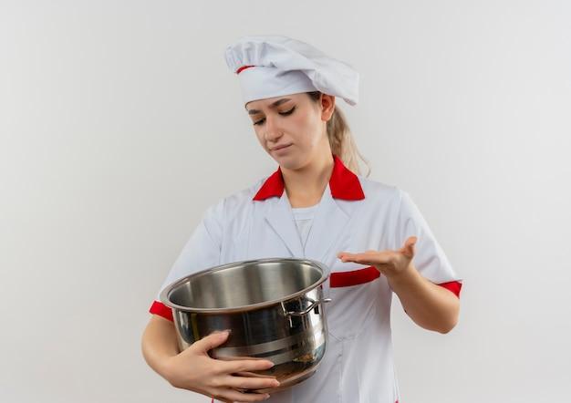 Onbehaagde jonge mooie kok in chef-kok uniform houden en kijken naar pot en wijzend op het met de hand geïsoleerd op witte ruimte