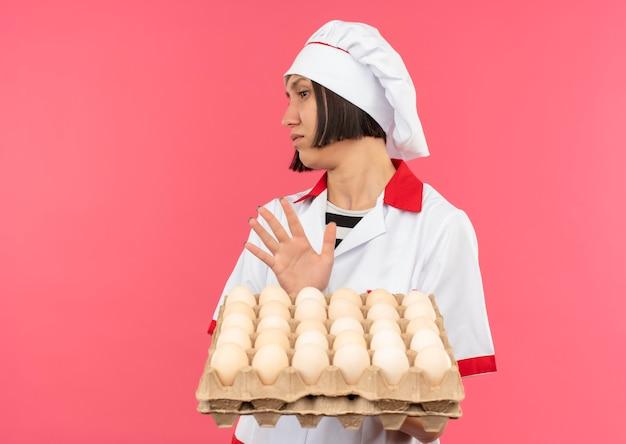 Onbehaagde jonge vrouwelijke kok in chef-kok uniform bedrijf karton met eieren kant kijken en gebaren niet geïsoleerd op roze achtergrond met kopie ruimte