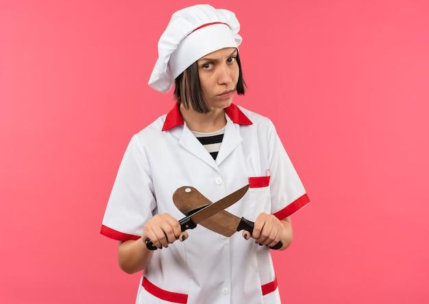 Onbehaagde jonge vrouwelijke kok in chef-kok uniform met mes en hakmes geïsoleerd op roze achtergrond met kopie ruimte