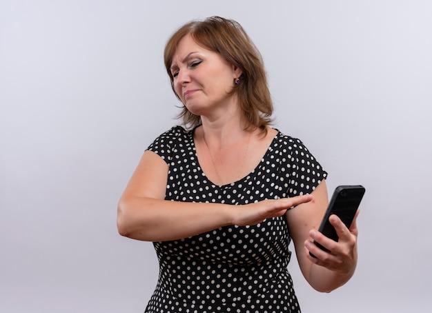 Onbehaagde vrouw van middelbare leeftijd die mobiele telefoon houdt en met de hand erop wijst op geïsoleerde witte achtergrond