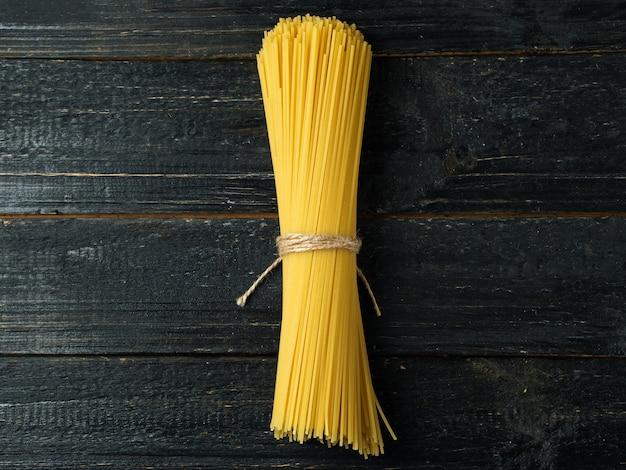 Onbehandelde droge pasta spaghetti band op donkere tafel
