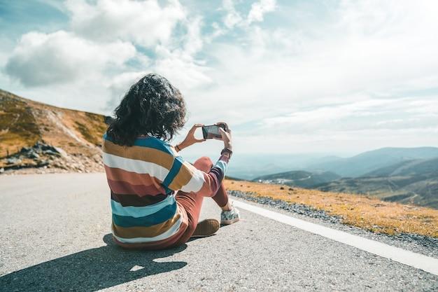 Onbekende jonge vrouw maakt foto van het landschap.