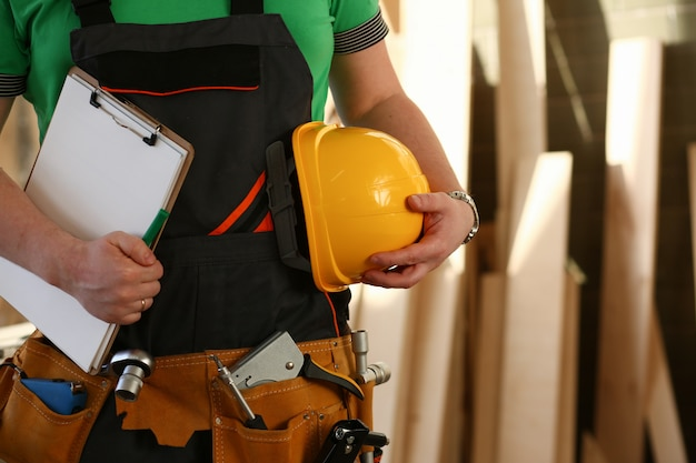 Onbekende klusjesman met handen op taille en gereedschapsriem met bouwgereedschap tegen grijze achtergrond. diy-tools en handmatig werkconcept