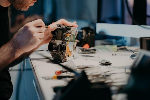 Onbekende man repareert professionele digitale camera, maakt gebruik van schroevendraaier