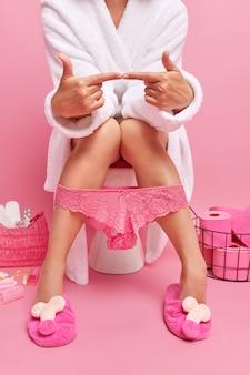Onbekende vrouw denkt aan iets terwijl ze op de toiletpot zit houdt wijsvingers tegenover elkaar overweegt over iets draagt witte badjas pantoffels slipje naar beneden getrokken op benen