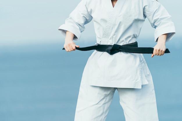 Onbekende vrouwelijke karate-atleet die zwarte riem op haar taille rijgt