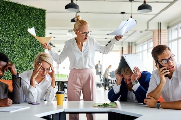 Onbeleefde boze vrouwelijke baas is ontevreden, geïrriteerd door werknemers, schreeuwt tegen hen, incompetente werknemers. in modern kantoor