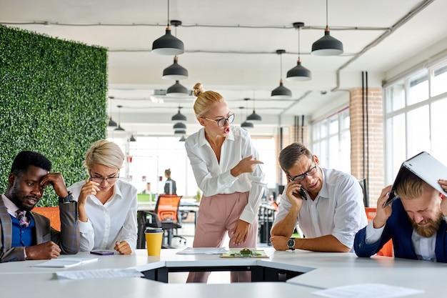 Onbeleefde boze vrouwelijke baas is ontevreden geïrriteerd door werknemers