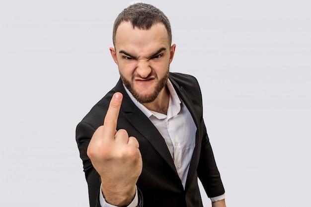 Onbeleefde jonge man in pak staat en toont neuken. hij kijkt op camera met boos gezicht.