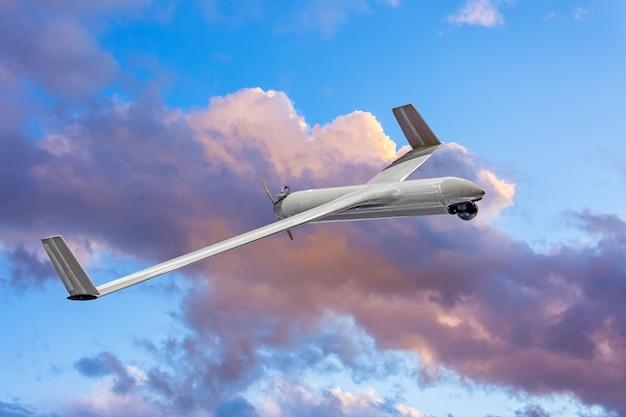Onbemande militaire drone op patrouilleluchtgebied bij zonsonderganghemelwolken.