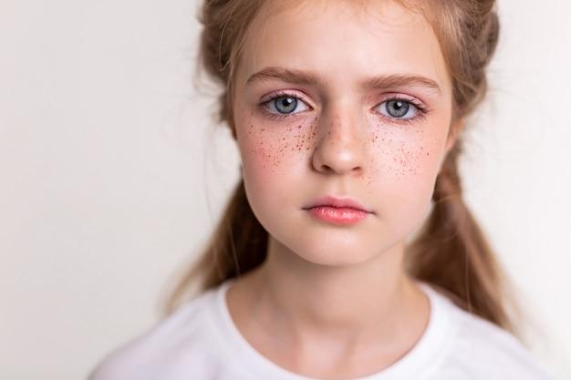 Onberispelijk klein kind. sceptische schattige dame die verdrietig en kalm is terwijl ze dichtbij poseert voor de camera
