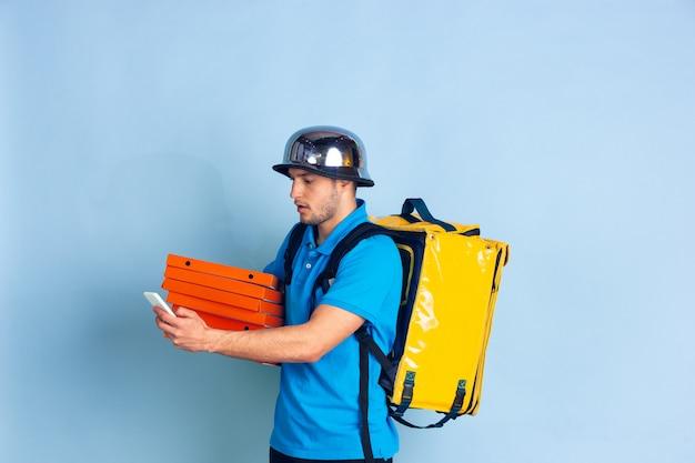 Onberispelijke bezorgservice tijdens quarantaine. man levert voedsel en boodschappentassen tijdens isolatie. emoties van bezorger die op blauw worden geïsoleerd