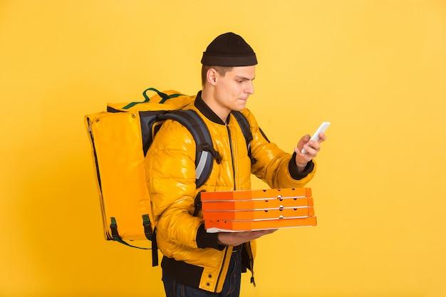 Onberispelijke bezorgservice tijdens quarantaine. man levert voedsel en boodschappentassen tijdens isolatie. emoties van bezorger die op geel worden geïsoleerd
