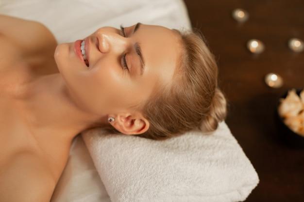Onberispelijke huid. glimlachende aantrekkelijke blonde dame die tevreden is met een ontspannende procedure tijdens een bezoek aan het professionele centrum