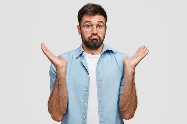 Onbewust geen idee van een bebaarde knappe man haalt zijn schouders op van onzekerheid