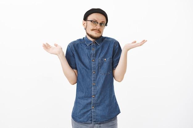 Onbewust knappe jonge clueless man met baard en snor in trendy hipster muts en bril schouder schouderophalend gebaar maken met opgeheven handpalmen kantelen hoofd en tuitende lippen onzeker