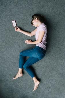 Onbewuste vrouw die op tapijt dichtbij mobiele telefoon ligt
