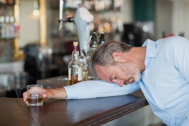 Onbewuste zakenman met whisky glas liggend op een teller
