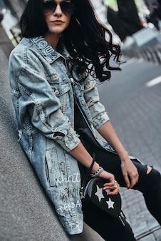 Onbezorgd genieten van de buitenlucht. aantrekkelijke jonge vrouw in spijkerjasje kijken camera