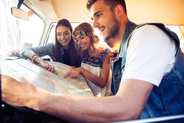 Onbezorgd weekend met vrienden. gelukkige jonge mensen in een vintage busje kijken naar een wegenkaart