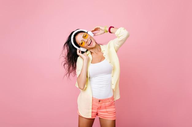 Onbezorgde aziatische vrouw die in zomerkleren favoriete liedje met gelukkige gezichtsuitdrukking zingt. indoor portret van fascinerende spaanse meisje in gele jas met plezier tijdens dans.