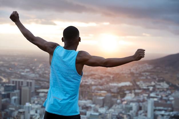 Onbezorgde onafhankelijke man met donkere huid, staat achterover, strekt zijn handen uit om de wereld vast te houden, voelt vrijheid, draagt een blauw vrijetijdsvest, geniet van een panoramisch uitzicht bij zonsopgang. recreatie concept