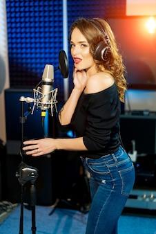 Ondenser microfoon met popfilter en trillingsdemper. professionele opname van het nummer in de studio. mooie vrouw in koptelefoon in de buurt van de microfoon.