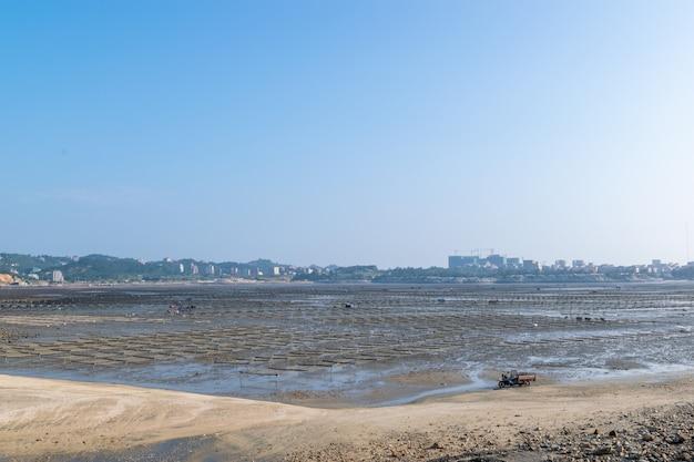 Onder de blauwe lucht de lijnen en texturen van bamboevlotten en touwen in de zeewierboerderij op het strand
