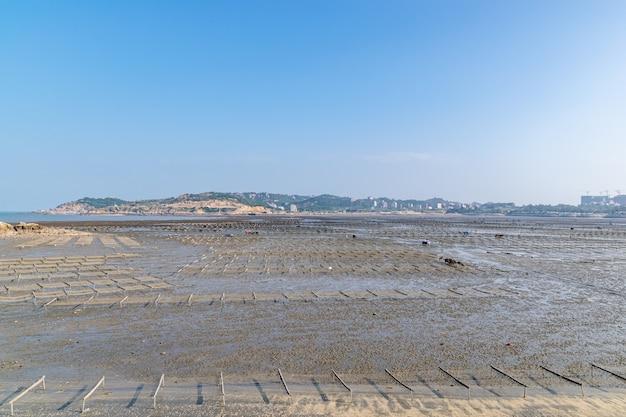 Onder de blauwe lucht zijn de lijnen en texturen van bamboevlotten en touwen in de zeewierboerderij op het strand erg netjes