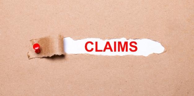 Onder de gescheurde strook kraftpapier bevestigd met een rode knop bevindt zich een wit papier claims