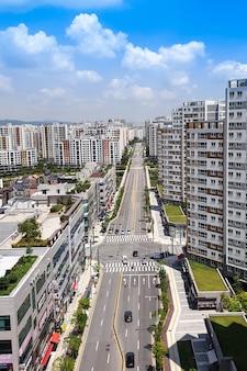 Onder de heldere hemel zijn er appartementen, gebouwen en auto's op de weg.