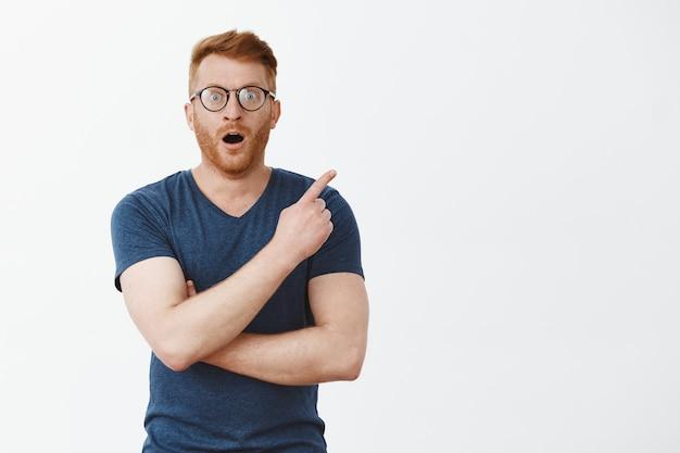 Onder de indruk aantrekkelijke blanke man met borstelharen in bril en blauw t-shirt, wijzend naar de rechterbovenhoek, hijgend en laat vallen van verbazing