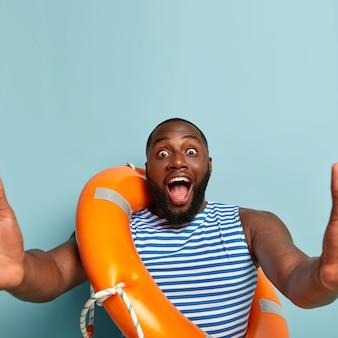 Onder de indruk afro-amerikaanse man heeft ogen uitgeklapt, houdt zijn mond open, handen gestrekt, maakt selfie