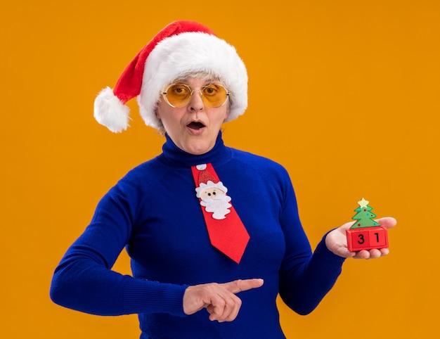 Onder de indruk bejaarde vrouw in zonnebril met kerstmuts en kerst stropdas bedrijf en wijzend op kerstboom ornament geïsoleerd op een oranje achtergrond met kopie ruimte
