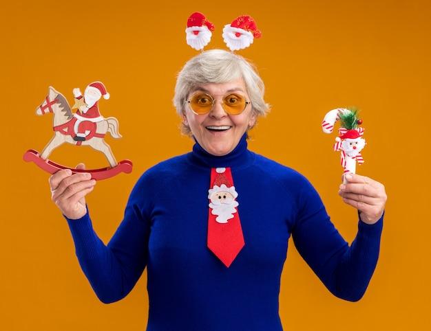 Onder de indruk bejaarde vrouw in zonnebril met santa hoofdband en santa stropdas santa houden op hobbelpaard decoratie en riet van het suikergoed geïsoleerd op een oranje achtergrond met kopie ruimte