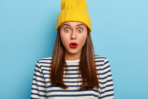 Onder de indruk bezorgde vrouw reageert op verbluffend gerucht, houdt de adem in, heeft afluisterogen, draagt gele hoed en gestreepte trui kan niet geloven in verbaasd nieuws, heeft rode lippen, minimale make-up
