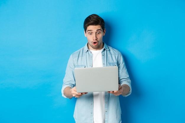 Onder de indruk blanke man die met verbazing naar het scherm van de laptop kijkt, promo op internet bekijkt, tegen een blauwe achtergrond staat