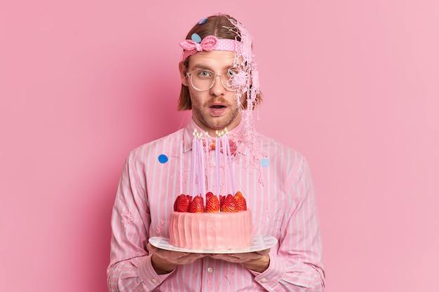 Onder de indruk blanke man reageert op iets verrassends viert verjaardag gaat kaarsen blazen en wensen gekleed in elegante kleding geïsoleerd over roze muur