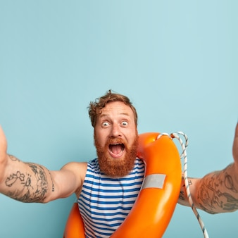 Onder de indruk blij verrast mannelijke zwemmer schreeuwt naar de camera, staart met afgeluisterde ogen, maakt selfie