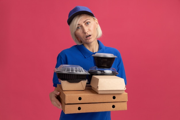 Onder de indruk blonde bezorger van middelbare leeftijd in blauw uniform en pet met pizzapakketten met voedselcontainers en papieren voedselpakket erop kijkend naar voren